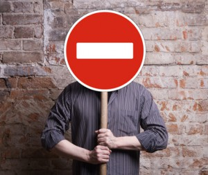 A man holds a sign forbidding face.
